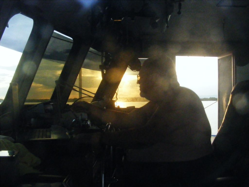 Bert at the helm of M/V Vagabond, off the coast of Belize, near Monkey Caye